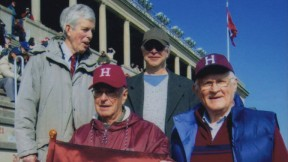 Alumnus Paul Lee '46 carries the (replica) Little Red Flag at the 2012 Harvard-Yale game. Steve Goodhue '51 is beside him; Spencer Ervin '54 and Jeff Lee '74 stand behind.