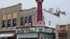 Photo of the exterior of Coolidge Corner Theater, with its vertical red neon sign.