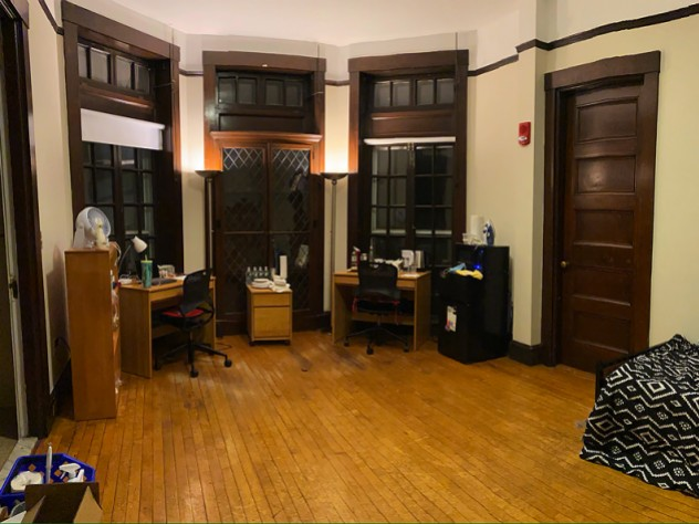 A large dorm room with desk, bed, lamps, and quarantine necessities, including bottled water, masks, and sanitizing supplies.
