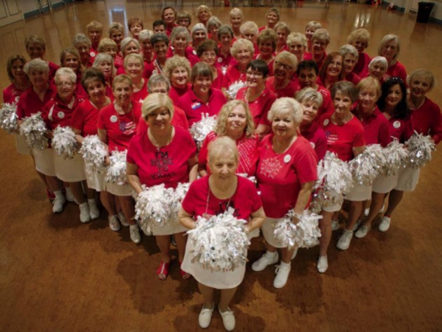 Photo of a cheerleader group composed of elderly women, all in red tops and white skirts, with pompoms