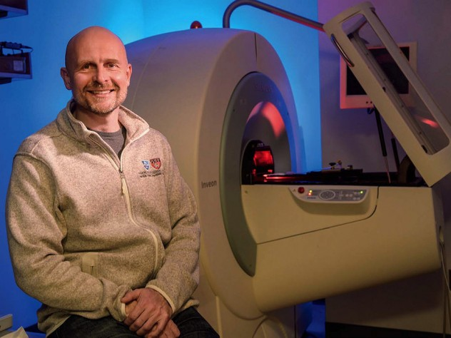 Matthias Nahrendorf seated in front of a PET/CT scanner