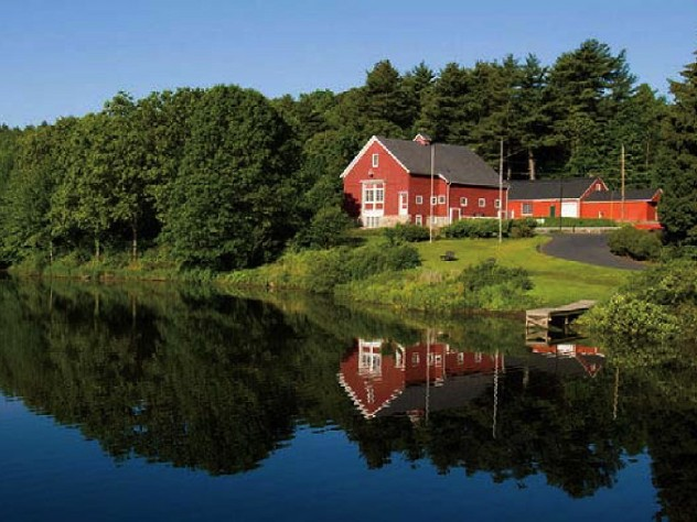 Iconic red-painted River Bend Farm Visitor Center by the Blackstone River and canal