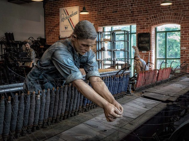 A replica of a textile mill shows life-like statues of workers.