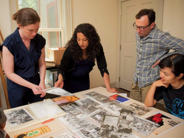 Hinton arranges materials for the Angela Davis exhibit with (from left) Radcliffe arts program manager Meg Rotzel, gallery coordinator Joe Zane, and Pforzheimer fellow Jackie Wang.