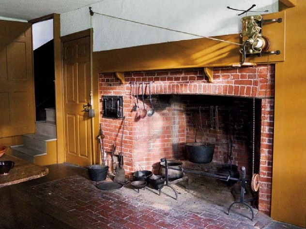 The main house kitchen, with a massive fireplace, and the narrow doorway to the service stairs.