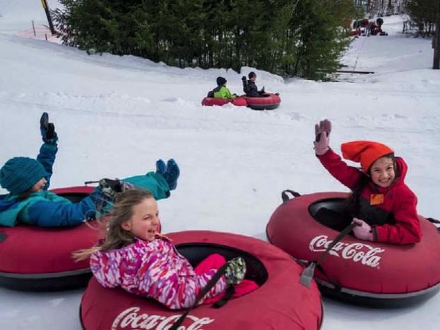 Kids in snow suits having fun snow-tubing