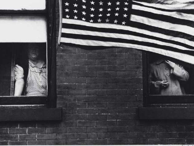 Robert Frank photograph of partially obscured people looking out of windows behind a large American flag