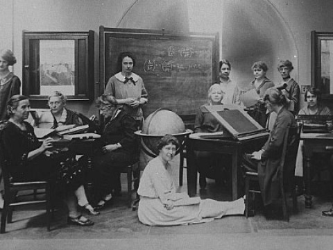 Several Harvard Computers and Radcliffe students pose for a photograph together, seated at desks and sitting on the floor
