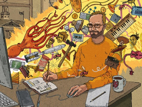 A professor sits at a computer whose screen is shooting out a beam of light filled with all sorts of animals and musical instruments
