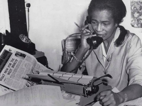 """Black journalist Claudia Jones on the phone in the offices of the """"West Indian Gazette"""" in London"""