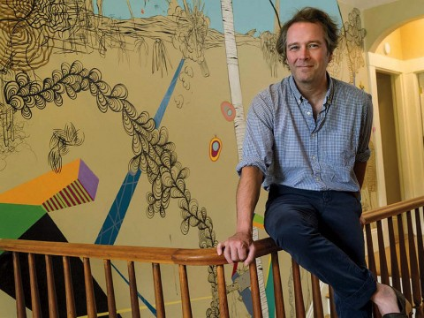 "Dan Chiasson at home in front of a ""sometimes delightful, sometimes disturbing"" mural by David Teng Olsen, which appears in The Math Campers."